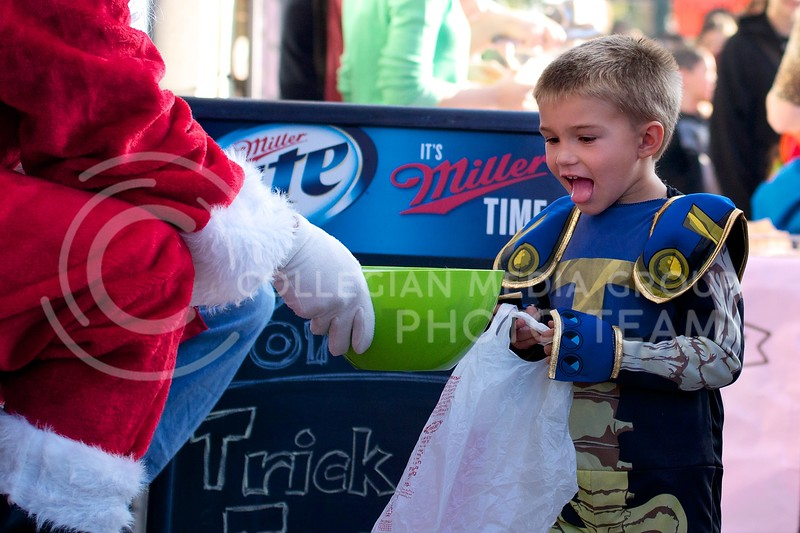 With tongue stinging out, a child excitedly stares at the bowl full of candy held out by Santa at Trick-or-Treat in Aggieville on October 25, 2013.