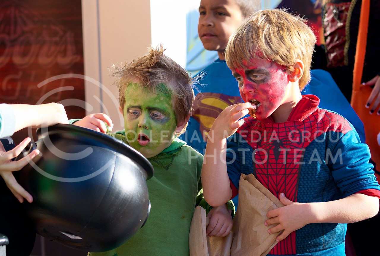 Jack Hutchinson (left), dressed as The Hulk, and his brother Caleb (right), suited up as Spider Man, pick out candy from a large bowl full during Trick-or-Treat at Aggieville on October 25, 2013.