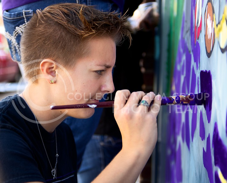 Bethany Huddleston, sophomore in biology and a member of Alpha of Clovia, brushes in purple bricks for their Wizard of Oz themed painting as part of Paint the 'Ville at Aggieville on Tuesday.