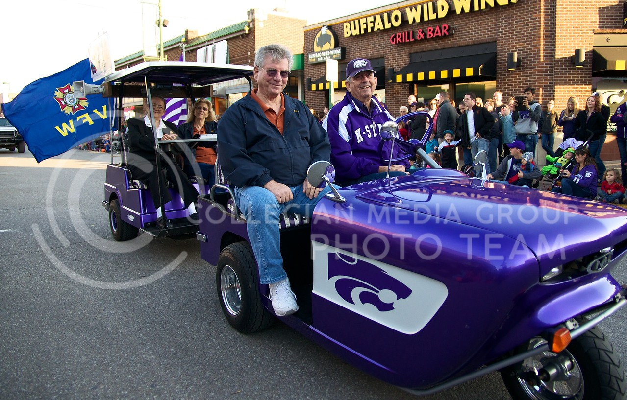 Members of the Veterans of Foreign Wars ride through Aggieville on a custom motorized tricycle as part of the 2013 K-State Homecoming Parade on October 25.