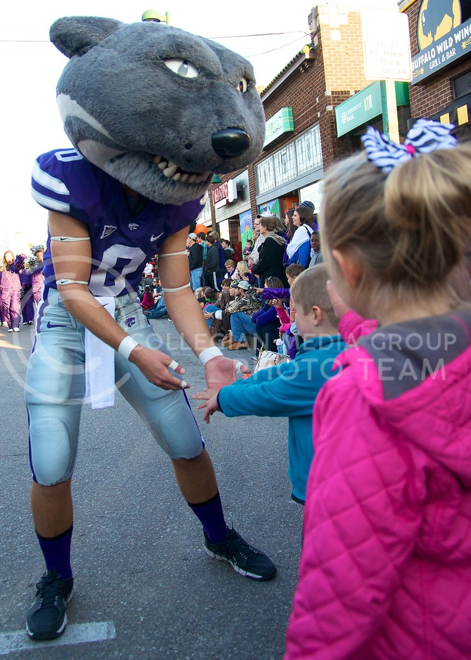 Willie greets and high-fives kids lined up on the sidewalk of Aggieville during the 2013 K-State Homecoming Parade on October 25.