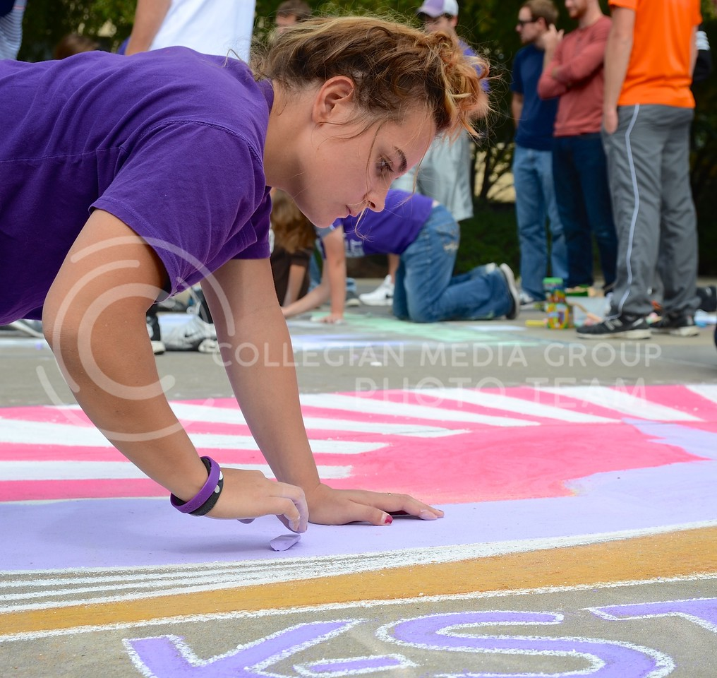 "Jennifer Stawski, sophomore in athletic training, smooths the chalk on the Japanese Yosakoi Dance Club's chalk art, featuring the rising sun behind Anderson Hall, during the Homecoming Sidewalk Chalking contest Sunday afternoon in Bosco Plaza. The theme for this year's Homecoming is ""A Tale of Tradition,"" which designers could interpret however they saw fit in their designs."