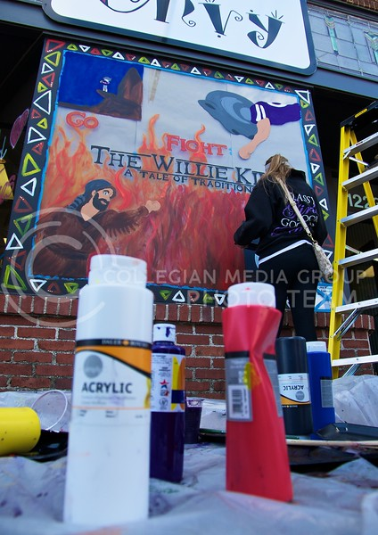 Ashley Pihl, a senior in hotel and restaurant management and a member of the Sigma Kappa Sorority, finishes up a Lion King themed painting during Paint the 'Ville at Aggieville on Tuesday.