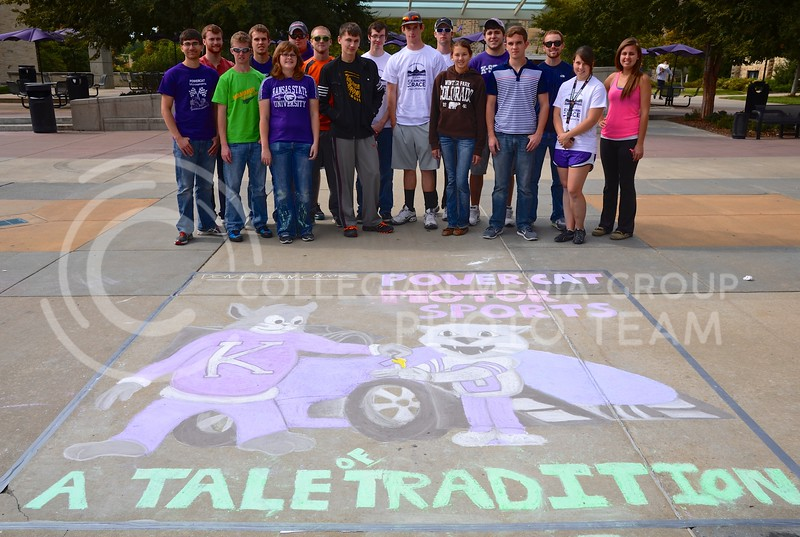 """Members of the Powercat Motor Sports design team stand with the sidewalk art they designed and chalked during the Homecoming Sidewalk Chalking contest Sunday afternoon in Bosco Plaza. The theme for this year's Homecoming is """"A Tale of Tradition,"""" which designers could interpret however they saw fit in their designs."""