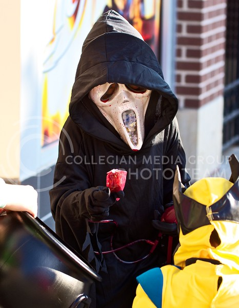 Jimmy Ramirez, wearing a Scream mask complete with oozing blood, picks out a piece of candy during Trick-or-Treat in Aggieville on October 25, 2013.