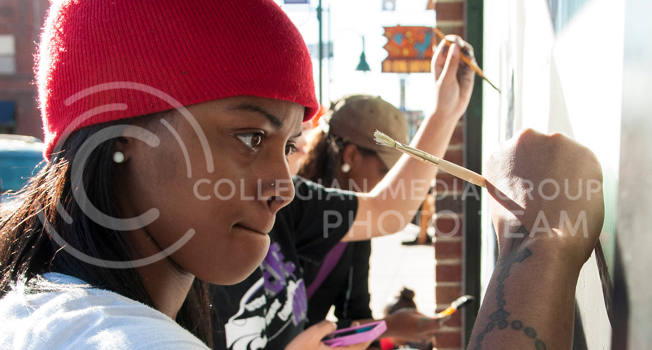 Nekole Hins, freshman in business administration, uses the blunt end of a paint brush to etch letters in the paint of the Black Student Union window in Aggievill in Oct.22, 2013.