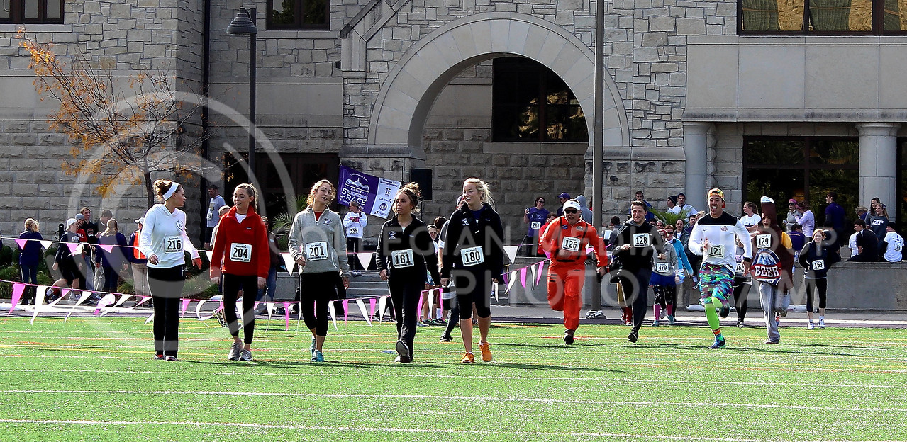 A group of women have a conversation on the way to the finish while the group of men behind them race each other in various costumes.