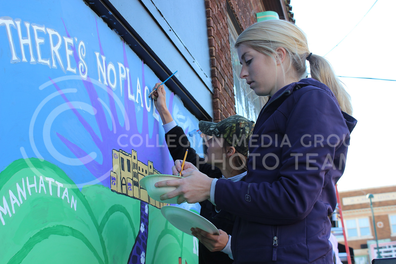 "Mallory Keating (Purple) and Lauren Currie of Chi Omega put finishing touches on their Wizard of OZ themed window painting for the ""Paint the Ville"" homecoming event."