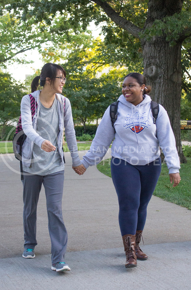 Tran Pham, a sophomore in mechanical engineering, walks hand-in-hand on campus with Brianna Chatmon, a sophomore in open option, on Oct. 8.<br /> <br /> The International Buddies program is desiged to help bring international students and domestic students together.