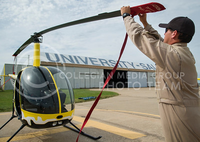 Eric Shafer, an instructor for K-State Salina contracted from Universal Helicopters, ties down the rotors after a flight with a student Wednesday morning at K-State Salina.  Shafer flew with student Bryan Brooks, who said the Kansas winds make flying the smaller R-22 helicopter even more difficult.