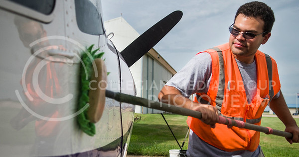 Jonathan Berroa, a senior in professional piloting, washes a plane at K-State Salina Thursday morning.   Washing the planes not only makes the planes look nice, but keeps the leading edge clean which makes for a smoother flight.