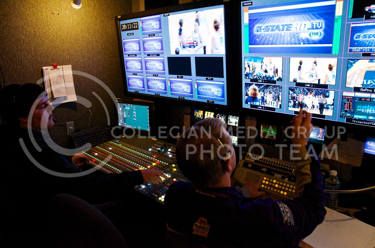 Broadcast director Andy Liebsch points out a camera feed, directing technical director Gardner Jordan, who is manning the video mixing board, to fade into it after the K-StateHD.TV logo.