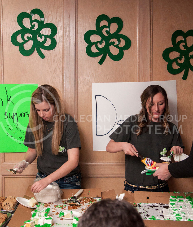 Hannah Sharp, sophmore, in business finance, and Kara Katenberg, senior in marketing, cut and serve cake to patrons of the Kappa Delta Shamrock Shootout on March 2 at the Kappa Delta house.