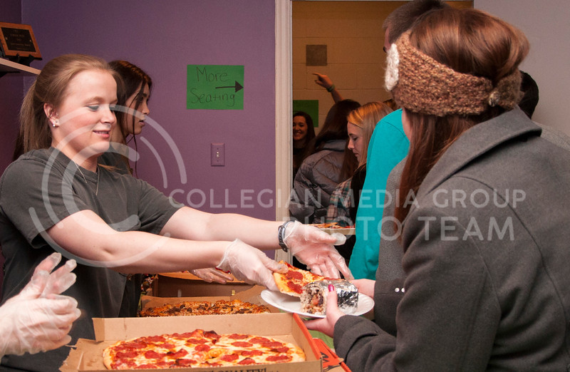 Hayley Parker, sophmore in animal science, serves pizza to patrons of the Kappe Delta Shamrock Shootout buffet dinner at the Kappa Delta house on March 2.