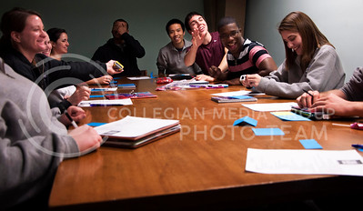 Hill, second from right, and the other West Hall RAs joke during a staff meeting in the West Hall basement on April 1. The RAs meet once a week with their residence life coordi- nator to discuss their work and life in the residence hall.