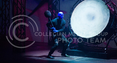 Crouching down to swing at a drum, one member of the Blueman Group keeps the beat during Wednesday's show.  The Blueman group will perform once again tonight at McCain.