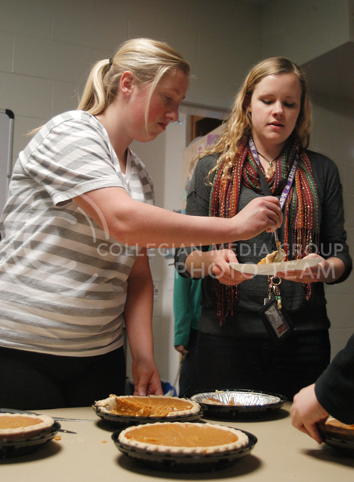 Megan Anderson, freshman in journalism, serves pie to Vicki Sears, junior in history, at the pie crawl in Ford Hall on Monday, Nov. 18. The proceeds of the event benefited K-State policeman, Sergeant Brian Sheaves, and his wife who has cancer.