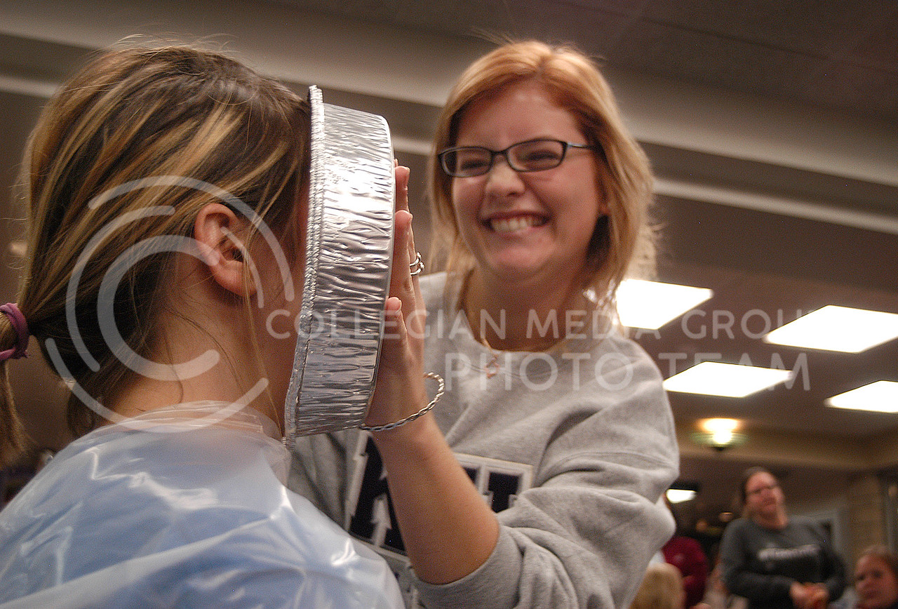 Sarah Hoffman, freshman in marketing, shoves whipped cream in the face of Alison Sharpe, junior in mechanical engineering, at the pie crawl in Ford Hall on Monday, Nov. 18. The proceeds of the event benefited K-State policeman, Sergeant Brian Sheaves, and his wife who has cancer.