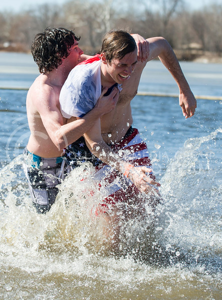 One member of the CSL team tackles another as they emerge from Tuttle Creek Lake after plunging on Feb. 22.