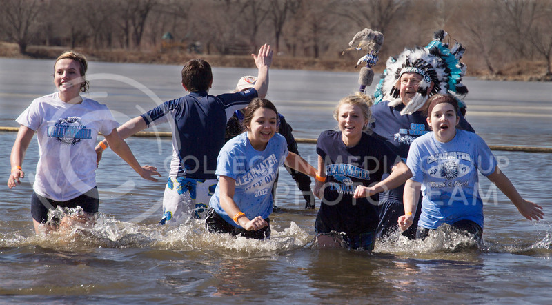 "A team races out of the chilly Tuttle Creek water after ""plunging"" in during the Polar Plunge on Saturday. The event is held to benefit the Special Olympics."