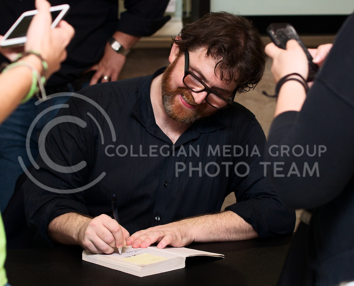 """Ernest Cline signs his book """"Ready Player One"""" for K-State students and faculty after speaking at McCain Auditorium on Thursday night."""