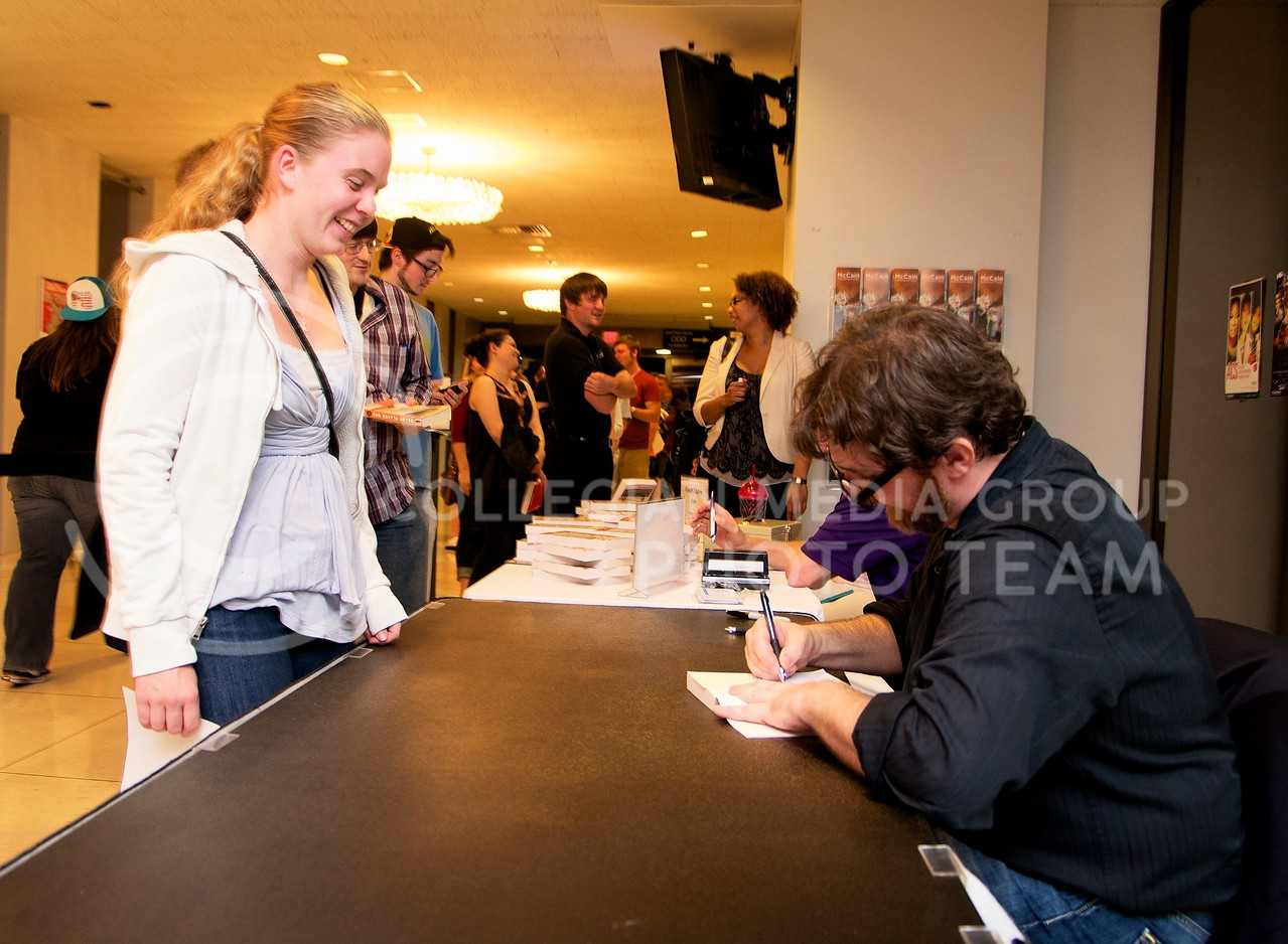 """Maria Neu, freshman in architecture, has her copy of """"Ready Player One"""" signed by Ernest Cline, the author, at McCain Auditorium on Thursday night.  Ernest Cline spoke to a large audience about his life and the story behind his novel."""