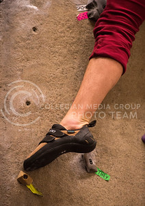 Brendan Heffernan, junior in phsyics, pushes off a foothold while climbing the rock wall at the Rec Center on Feb. 19.
