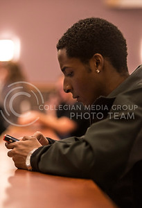 Arthur Bolton, junior in public relations, checks his phone before Mass Communications in Society in the Umberger lecture hall on Feb. 19.