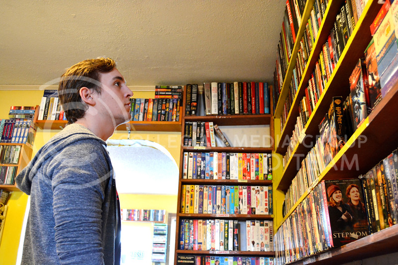 Felix Theriault-Briand, senior in communication studies, gazes at the many full shelves of books at the Grand Ol' Trunk Thrift Shop in Manhattan, KS on February 15.