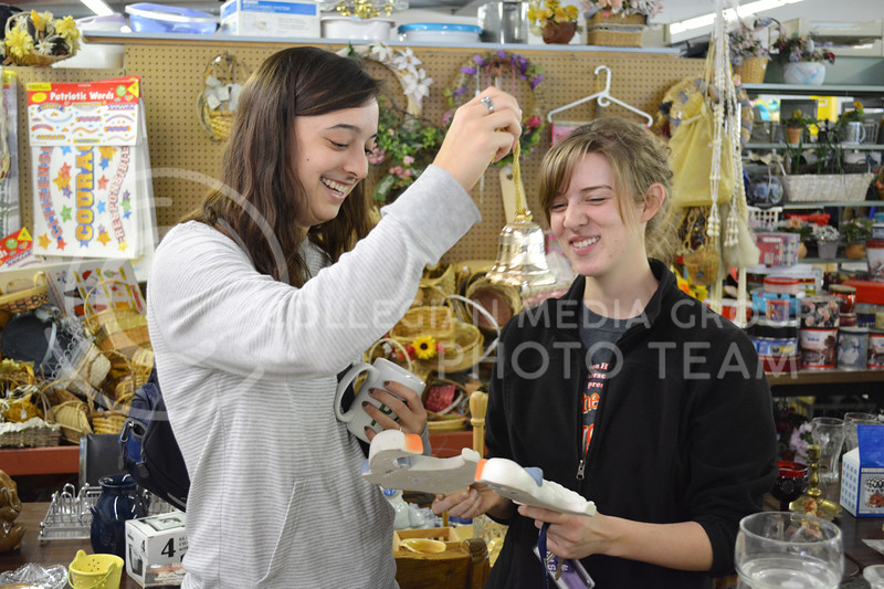 Abigail Hegarty, sophomore in pre-nursing, shows her friend Hannah Martin, sophomore in English ed, a bell at the Grand Ol' Trunk Thrift Shop in Manhattan, KS on February 15.
