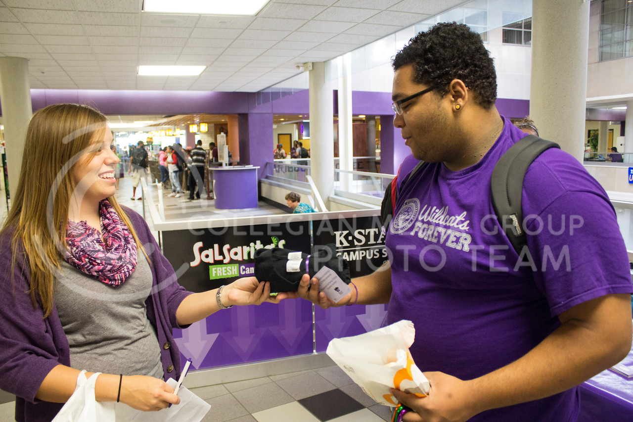 """Kris Larson, a senior in mechanical engineering, and a member of Student Alumni Board, gives a T-shirt to Alex Maupin, a freshman in Psychology, in the Student Union, Friday, Oct. 11, 2013.<br /> <br /> Wildcats Forever is an organization open for all K-State students to join. Its goal is to establish an early connection between students and the Alumni Association. One of the activities done by Wildcat Forever is """"Big 12 Fridays,"""" which occurs every Friday before a home Big 12 football game. On these days, any spotted Wildcats Forever member wearing their shirt is given a prize such as a glass cup, T-shirt, or gift certificate."""