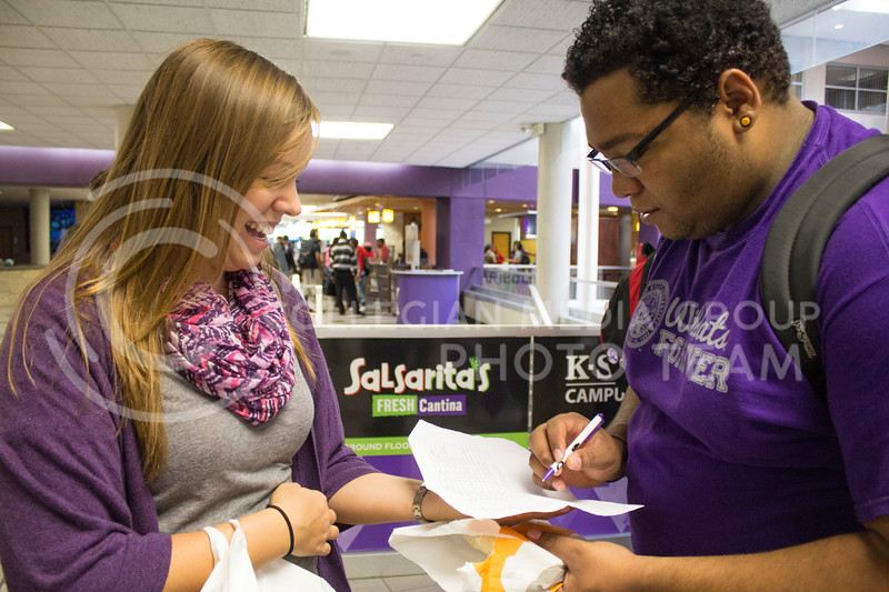 """Kris Larson, a senior in mechanical engineering, and a member of Student Alumni Board, has Alex Maupin, a freshman in Psychology, fill out his name to get a Wildcats Forever T-shirt, in the Student Union, Friday, Oct. 11, 2013.<br /> <br /> Wildcats Forever is an organization open for all K-State students to join. Its goal is to establish an early connection between students and the Alumni Association. One of the activities done by Wildcat Forever is """"Big 12 Fridays,"""" which occurs every Friday before a home Big 12 football game. On these days, any spotted Wildcats Forever member wearing their shirt is given a prize such as a glass cup, T-shirt, or gift certificate."""