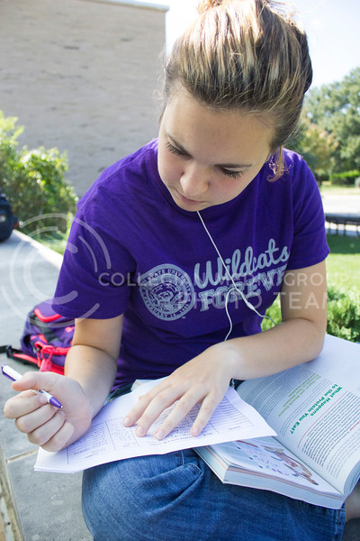 """Lindsay Adams, a freshman in nutrition, signs her name to get a free shirt at Bosco Plaza, Friday, Oct. 11, 2013.<br /> <br /> Wildcats Forever is an organization open for all K-State students to join. Its goal is to establish an early connection between students and the Alumni Association. One of the activities done by Wildcat Forever is """"Big 12 Fridays,"""" which occurs every Friday before a home Big 12 football game. On these days, any spotted Wildcats Forever member wearing their shirt is given a prize such as a glass cup, T-shirt, or gift certificate."""