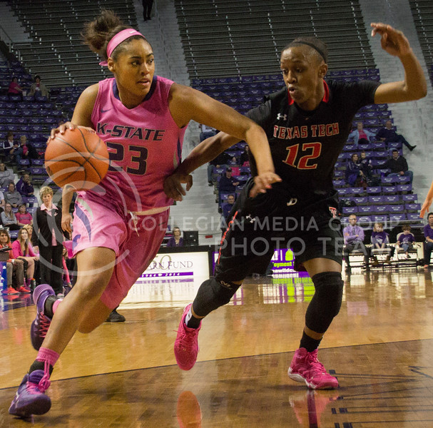 Ashia Woods, junior guard, drive the ball with Amber Battle defending her. Woods had seven rebounds on Saturday at Bramlage Coliseum against the raiders.