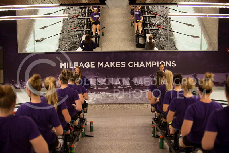 The women of the varsity rowing team watch themselves in mirrors above and to the sides of the practice tanks during practice in the tank room on Feb. 13.