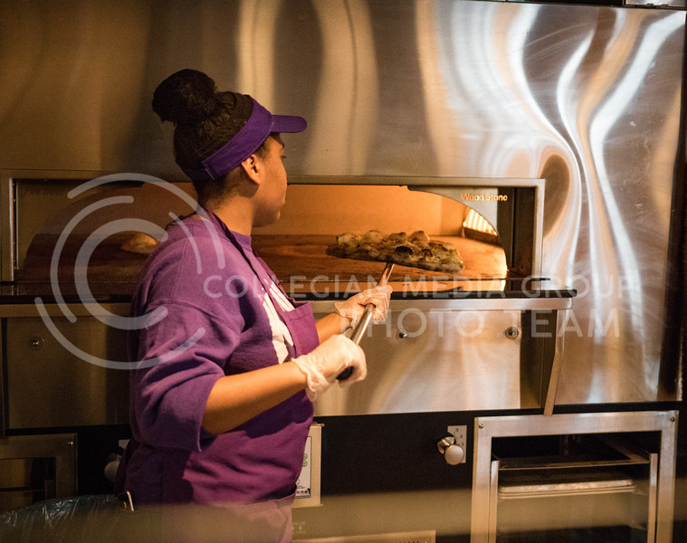 A Kramer worker removes pizza from the pizza oven in the Kramer Dining Center on Feb. 1, 2017. (John Benfer | Royal Purple)
