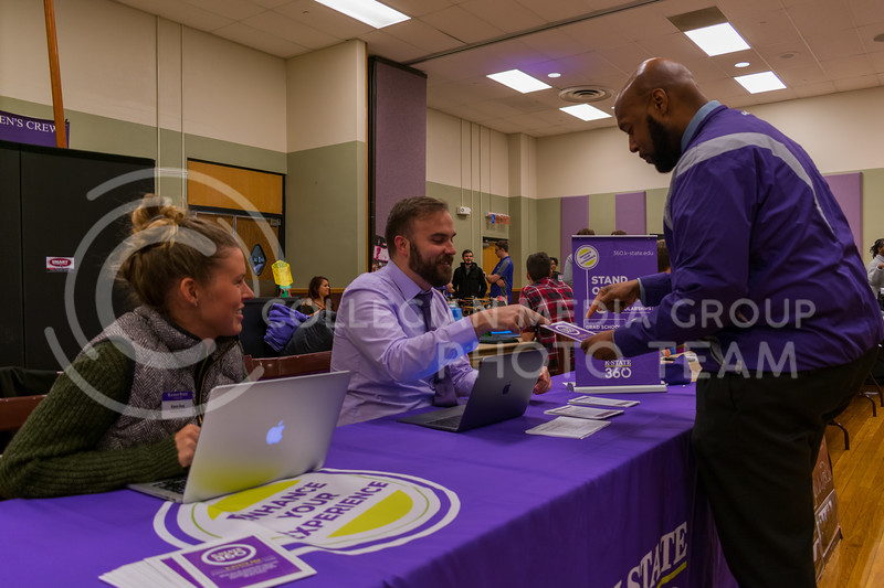 Graduate assistant, Kara Guy, watches as program coordinator, Trent McGee, discusses the features of K-State 360 during the Wildcat Winter Expo in the Union Ballroom on January 18, 2018. (Alex Todd | Collegian Media Group)