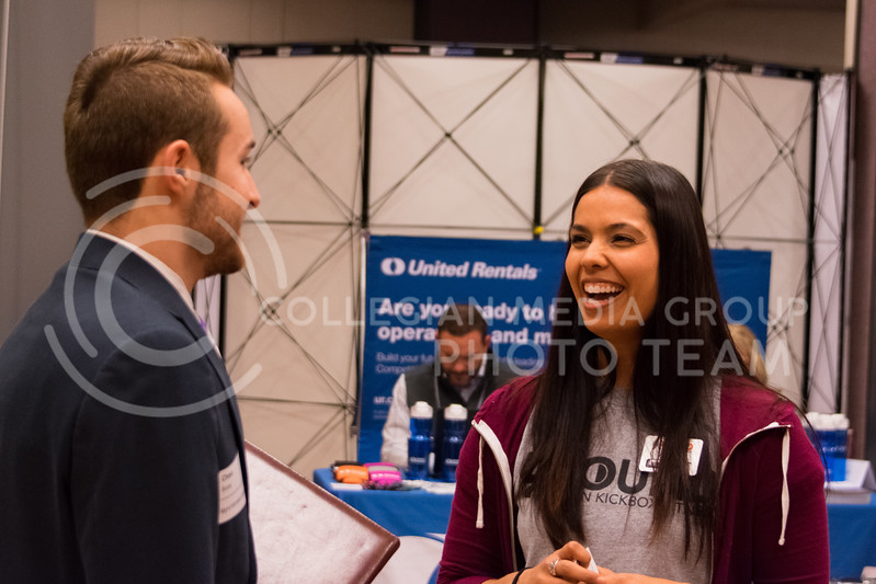 A representative from 9Round Fitness jokes with a student while discussing career opportunities at the business career fair on February 21, 2018 in the union ballroom. (Alex Todd | Collegian Media Group)
