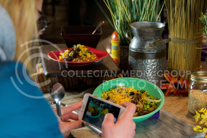 """Elly Dahl, freshman in Arts and Sciences, leans in close to get the perfect shot of her lunch during """"Cultivate You"""" at Kramer Dining Center on February 21, 2018. (Alex Todd 