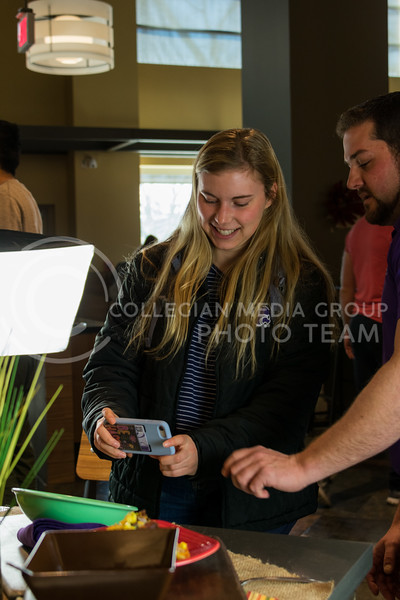 """A K-State student snaps a quick pic of her lunch during """"Cultivate You"""", put on by K-State Housing and Dining in Kramer Dining Center on February 21, 2018. (Alex Todd 