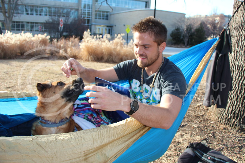 "Dane Davis, graduate student in strategic communication, hammocks with his rescue mix, Mogli, north of Kedzie Hall on Tuesday afternoon. Davis said he and Mogli spend so much time together that people sometimes recognize Davis as ""the guy with the dog."" Mogli is trained to obey hand signals, Davis said. (Tiffany Roney 
