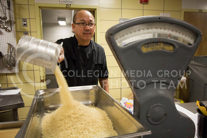 A chef measures out rice in a pan to begin preparing lunch for that day at the Derby Dining Center on March 2, 2018. ( Sabrina Cline | Collegian Media Group)
