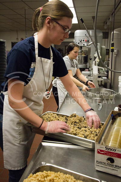 Two cooks prepare dessert for lunch in the bakery at the Derby Dining Center on March 2, 2018. ( Sabrina Cline | Collegian Media Group)