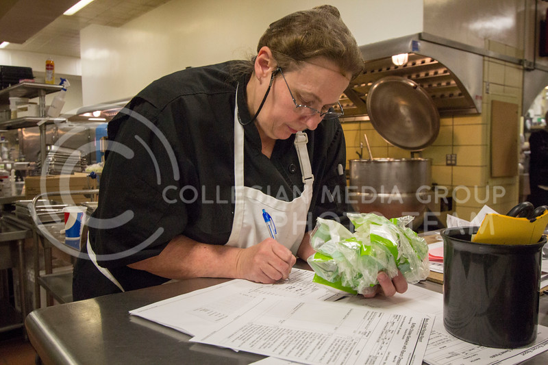 A chef reads and follows the recipe as she prepares for lunch that day at the Derby Dining Center on March 2, 2018. ( Sabrina Cline | Collegian Media Group)