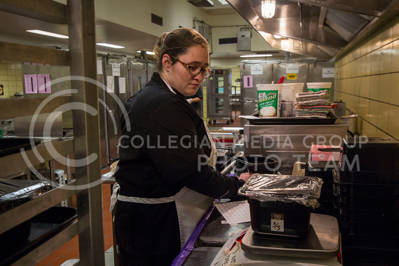 A chef at the Derby Dining Center weighs vegetables before preparing food at the Derby Dining Center on March 2, 2018. ( Sabrina Cline | Collegian Media Group)