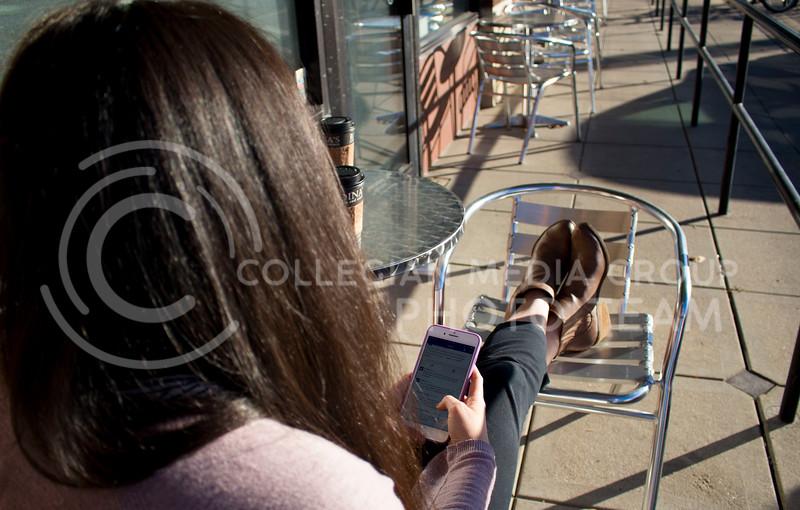 Christina DeGraffenreid, senior in speech pathology and gerontology, checks her phone outside Radina's in Aggieville on Nov. 8, 2017. (Abby Cambiano | Collegian Media Group)
