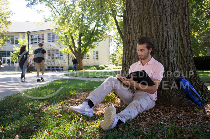 Business student and sophomore Andrew Breen enjoys the nice weather and shade out by Holtz Hall on October 2nd, 2017. (Kelly Pham | Royal Purple)