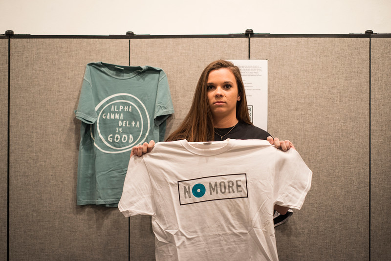 "Holding up a ""No More"" shirt, Wildcats Against Sexual Violence President Paige Eichkorn stands in front of her clothes in the ""What were you wearing?"" Gallery. ""No More"" is a movement created to spread awareness against sexual violence.<br /> Kevin Thompson 