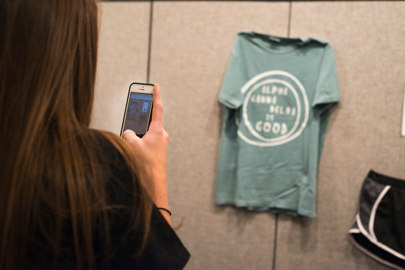 "In the ""What were you wearing?"" Gallery, Alpha Gamma Delta Member Paige Eichkorn takes a picture of her clothes on the display. Eichkorn has since created the club Wildcats Against Sexual Assault and acts as the club's president. <br /> Kevin Thompson 