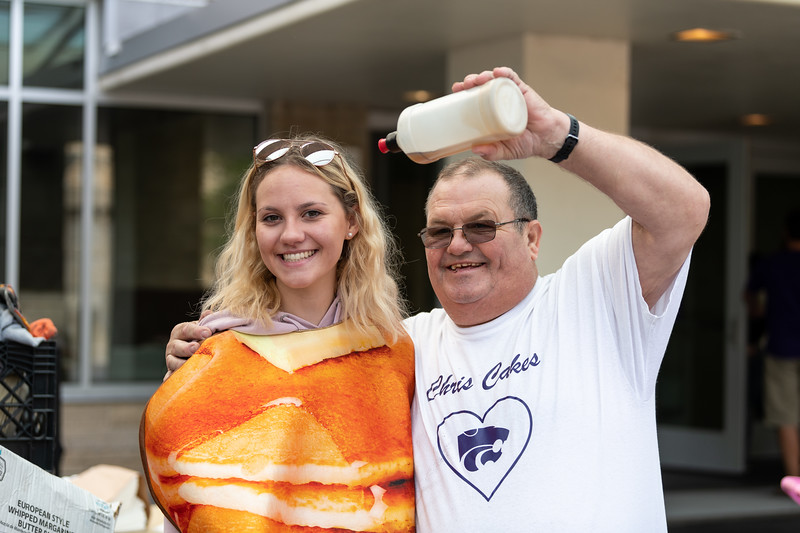 UPC Daytime Programs chair Bethany Rich poses as a pancake with Pat from Chris Cakes at the Kansas State Farmers' Market in Bosco Student Plaza on September 26, 2018. (Alex Todd | Collegian Media Group)